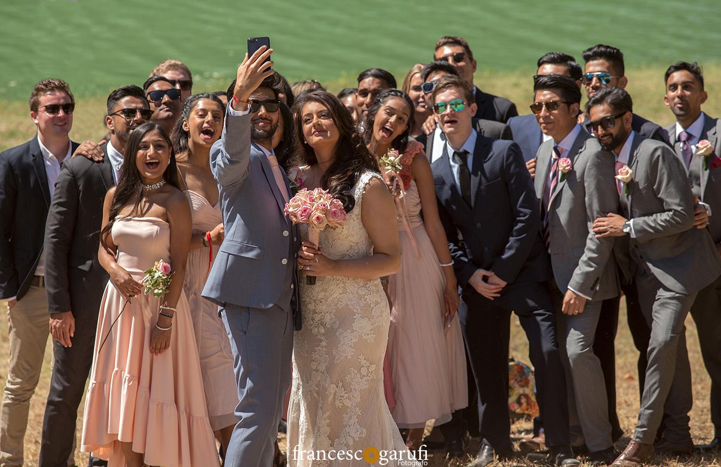 foto di gruppo di due sposi indiani con gli invitati